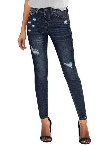 Front view of model wearing dark blue high-rise ripped skinny denim jeans