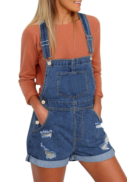 Front view of model wearing dark blue rolled hem ripped shorts denim bib overall
