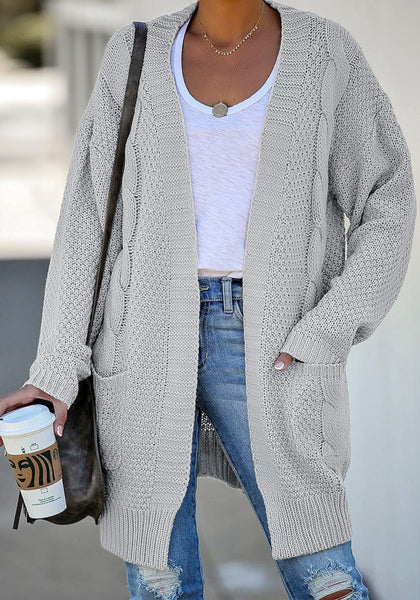 Front view of model wearing grey open-front oversized cable knit cardigan