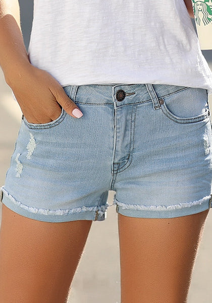 Front view of model wearing light blue frayed roll-hem ripped denim shorts