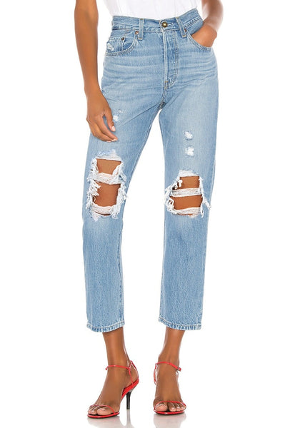 Front view of model wearing light blue high-waist ripped denim cropped jeans