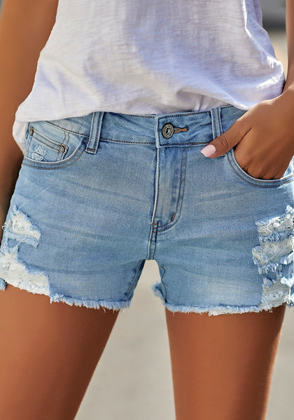 Front view of model wearing light blue raw hem distressed faded denim shorts