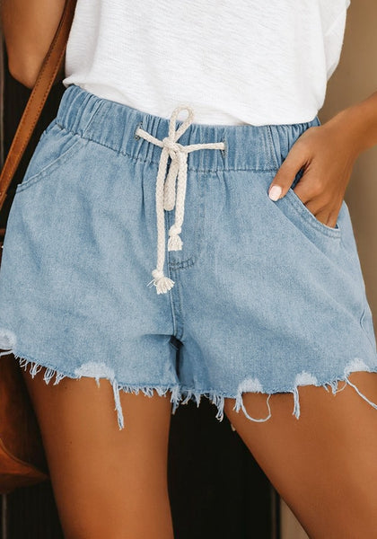 Front view of model wearing light blue raw hem high-waist drawstring denim shorts