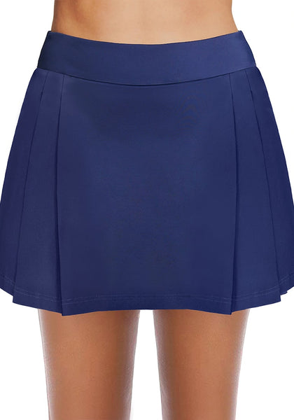 Front view of model wearing navy blue pleated side mid-waist swim skirt