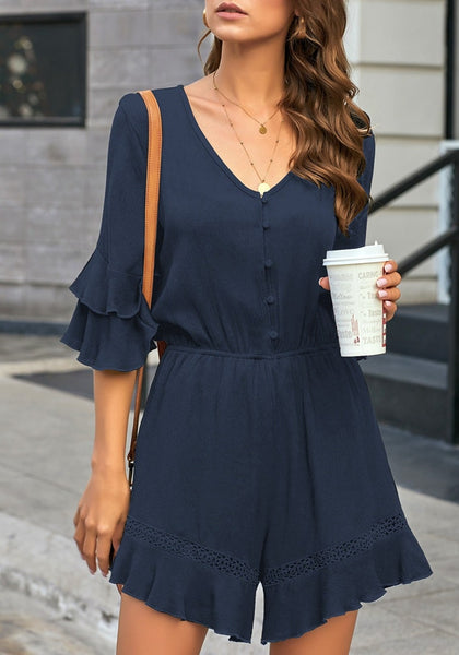 Front view of model wearing navy ruffle 34 sleeves elastic-waist button loop romper