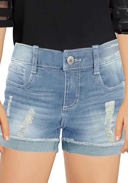 Front view of young model wearing faded blue cuffed hem ripped girls' denim shorts