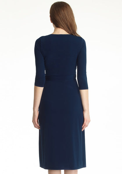 Full back shot of model in navy blue sweetheart neckline wrap dress