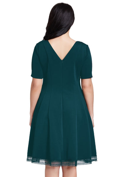 Full back view of woman in plus size deep green short-sleeves skater dress