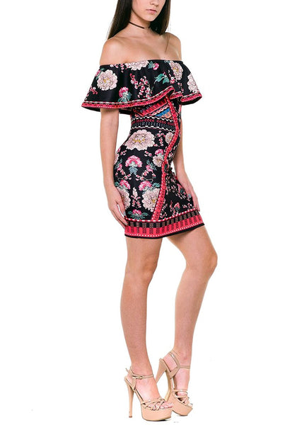 Full body angled side shot of model in floral ruffled off-shoulder dress