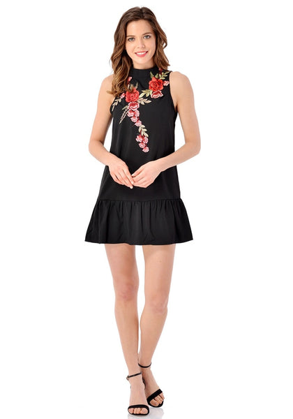 Full body front shot of model in black mock neck floral embroidered dress