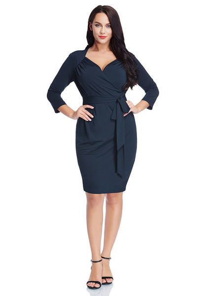 Full body front shot of model in plus size navy sweetheart wrap midi dress