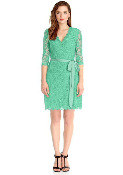 Full body front shot of woman wearing mint green lace overlay plunge wrap-style dress