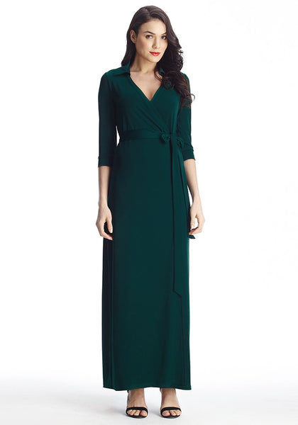 Full body shot of dark-haired lady in dark green plunge wrap belted maxi dress