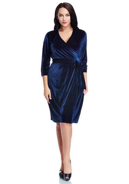 Full body shot of model in plus size navy blue velvet wrap dress