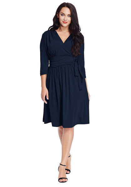 Full body shot of model wearing plus size navy blue plunge tie-side wrap dress