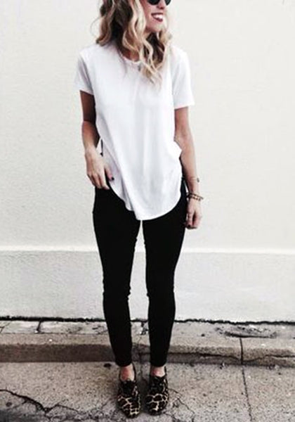 Full body shot of woman in white curved hem classic tee and black jeans