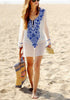 Full body shot of woman in white floral embroidered v neck beach cover-up by the beach