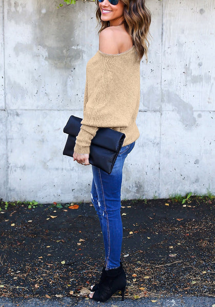 Full body side shot of woman in khaki off-shoulder bat sleeves sweater