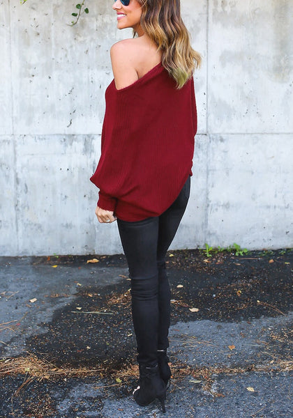 Full body side view of model in burgundy off-shoulder bat sleeves sweater