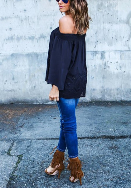 Full body side view of woman in navy blue off-shoulder hollow out hem top