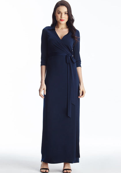 Full front shot of brunette model in navy blue plunge wrap belted maxi dress