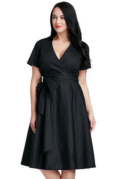 Full front shot of lady in plus size black surplice midi dress