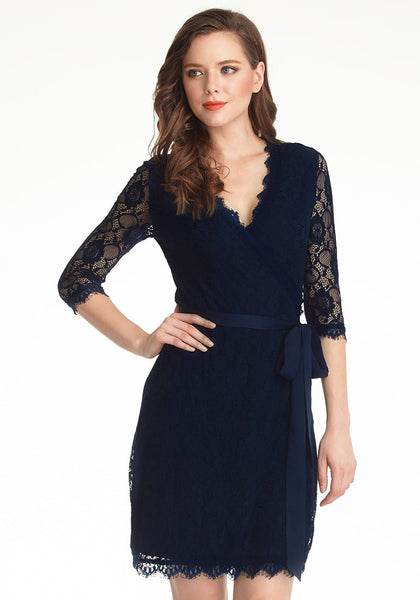 Full front view of model in navy blue lace overlay plunge wrap-style dress