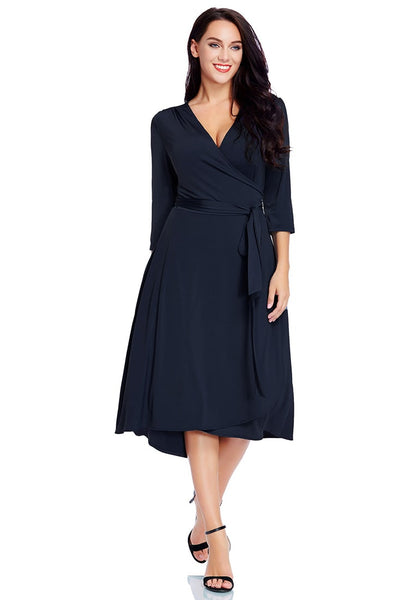 Full front view of model wearing plus size navy high-low wrap skater dress