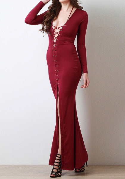 Full left angled shot of model in a burgundy lace-up long dress
