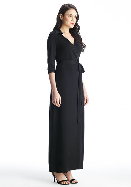Full right side view of model in black plunge wrap belted maxi dress