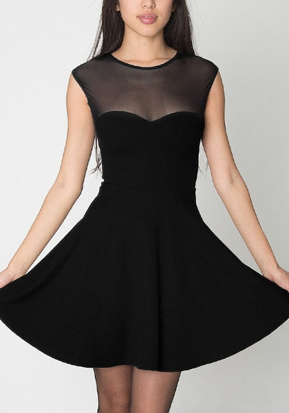 Full shot of model in black illusion-neck sleeveless mini dress