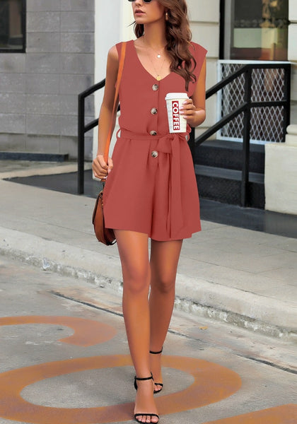 Full body shot of model in coral pink V-neck sleeveless belted button-up romper