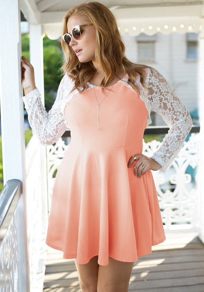 Girl in an apricot lace sleeve skater dress looking over the balcony