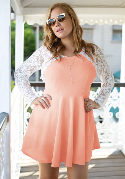 Girl in an apricot lace sleeve skater dress with hands akimbo