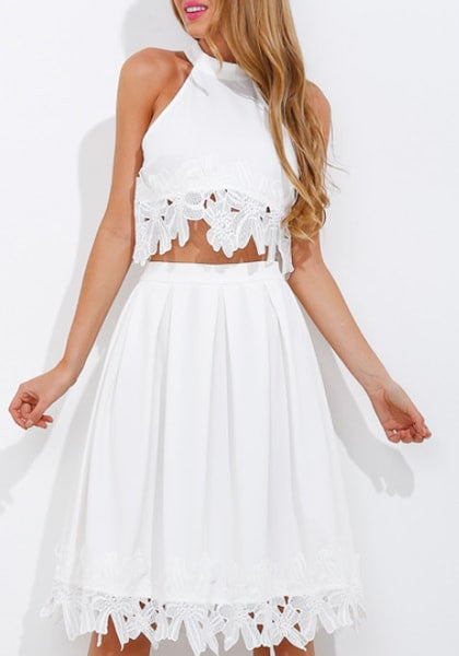Girl in white lace-appliqué high-neck crop top and white skirt