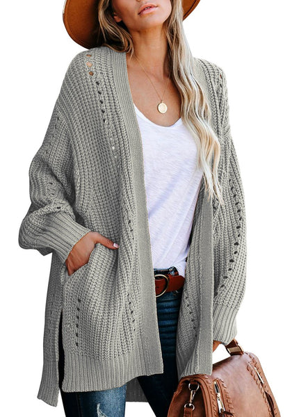 Front view of model wearing grey open-front side slit oversized cable knit cardigan