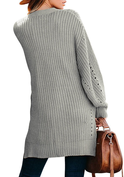 Back view of model wearing grey open-front side slit oversized cable knit cardigan