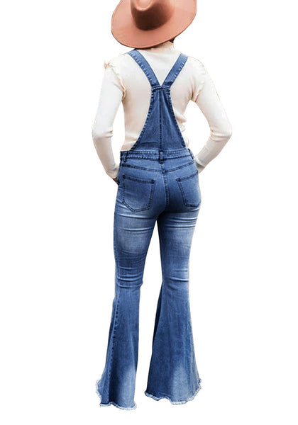 Back view of model wearing dark blue bell bottom ripped denim bib overall jumpsuit