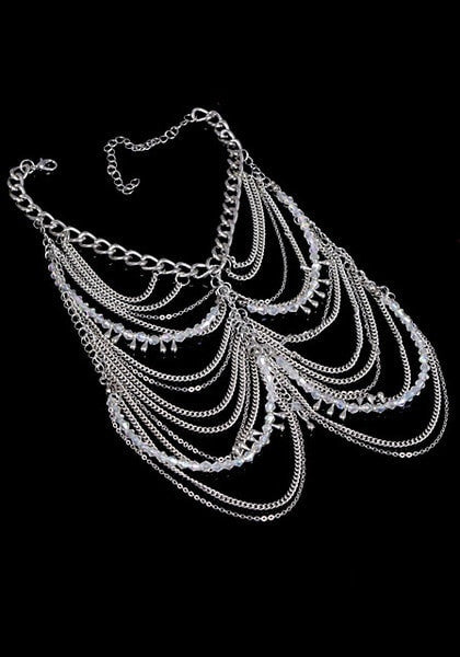 Layered silver chain anklets in black background