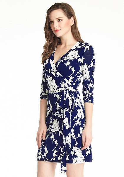 Left angle shot of model in navy blue floral plunge wrap dress