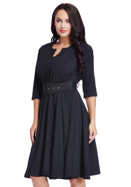 Left angle shot of model in plus size black belted skater dress