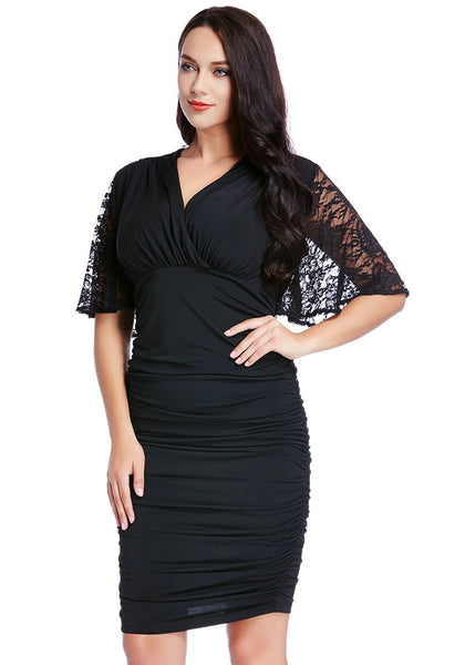 Left angle shot of model in plus size black ruching bodycon dress