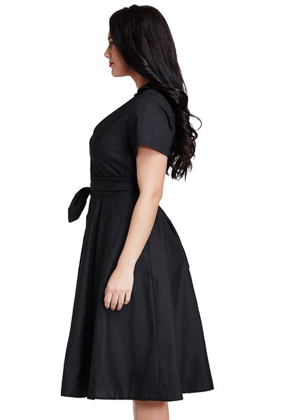 Left angle shot of model in plus size black surplice midi dress