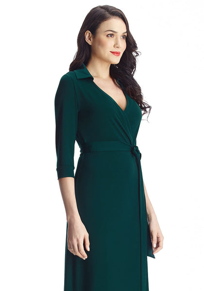 Left angled shot of brunette in dark green plunge wrap belted maxi dress
