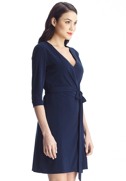 Left angled shot of brunette in navy plunge wrap-style belted dress