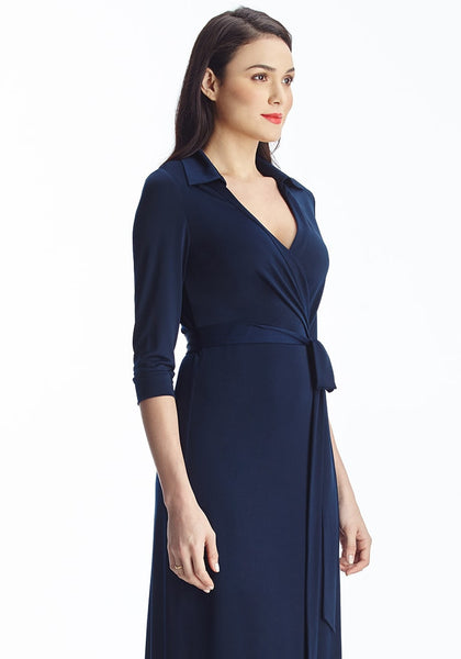 Left angled shot of brunette woman in navy blue plunge wrap belted maxi dress