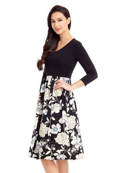 Left angled shot of model in black floral-bottom V neckline crop sleeves skater dress