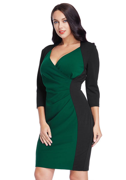 Left angled shot of model in plus size green raglan sleeve dress