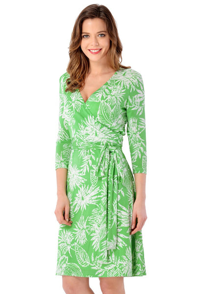 Left angled shot of model wearing light green plant-print crop sleeves faux wrap dress
