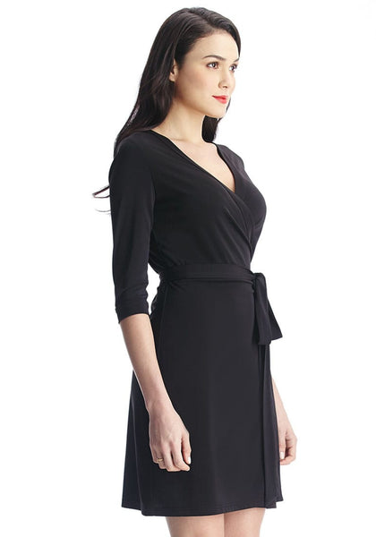 Left angled shot of woman wearing black plunge wrap-style belted dress